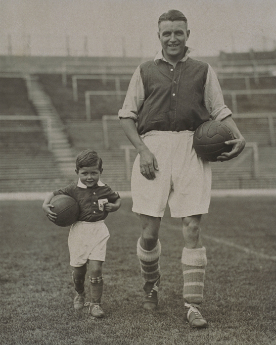Allenamento dell'Arsenal, 1934 © Daily Herald / National Media Museum, Bradford / SSPL Raffigurato il capitano dell'Arsenal e dell'Inghilterra Eddie Hapgood (1908-1973) e suo figlio, mascot dell'Arsenal ad Highbury, Londra